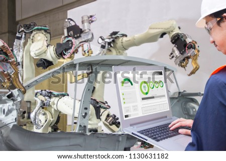 Industry 4.0 Robot concept .Engineers use laptop computers for machine maintenance, automation tools, .Close up of a robot arm in a car manufacturing department.