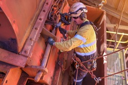 Industry rope access rigger abseiler high risk worker wearing fall safety body  harness working at height wearing a safety orange and black earmuffs noise protection while hammering using hammer