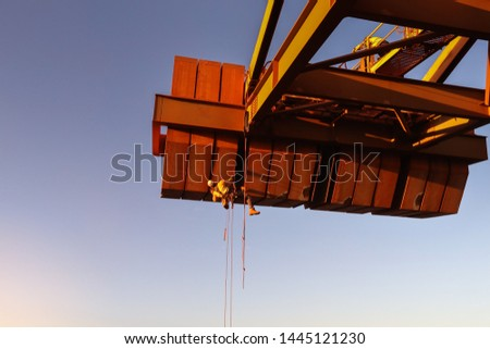 Industry rope access technician inspector wearing fall body safety harness abseiling working at height inspecting defect of concrete spalling on counterweight construction site Sydney, Australia
