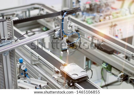 Industry 4.0 smart factory concept; artificial intelligence in production. Gripper picks up the product from automated car. Selective focus.