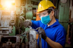 Industry worker wearing glass, ear phone and safety uniform used Vernier caliper to measure the object control operating machine working in factory wearing safety mask to protect for pollution.