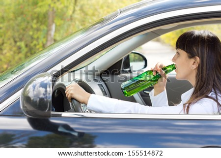 Inebriated female driver drinking alcohol directly from the bottle as she steers her car along the road posing a danger to others