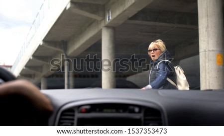 Inexperienced automobilist driving car city, scared woman running away, danger Stockfoto ©