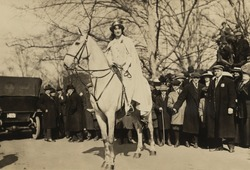 Inez Milholland, wearing white robes and a crown riding a white horse as the 'Herald' in the Women's Suffrage parade of March 3, 1913, the day prior to Woodrow Wilson's inauguration.
