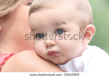 Infant baby boy in mother's arms