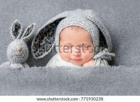 Stock Photo Infant baby boy sleeping under blanket