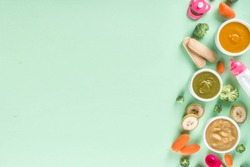 Infant baby food. Bowls with vegetable fruit puree, green, orange, yellow colors - broccoli, carrots, banana, apple. With baby accessories and toys green background Flat lay top view copy space