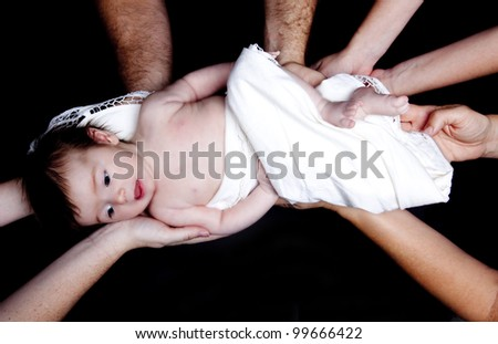 Infant baby girl held by many hands as though supported by  family or by the community perhaps for a blessing or other  religious ceremony over black backdrop.