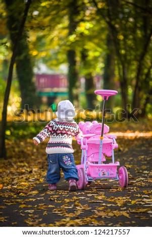 Infant baby girl in golden autumn park