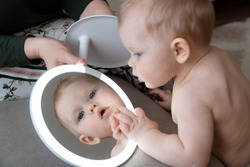 Infant baby girl play with mirror electronic lighted and look on to her own reflection. Mother care little child and help her