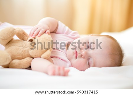infant baby girl sleeping with plush toy #590317415