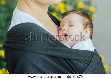 Infant baby sleeping in a wrap