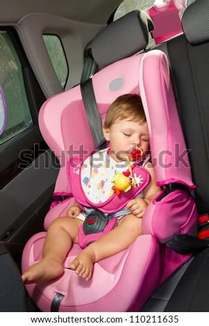Infant baby sleeps peacefully secured with seat belts while in the car.