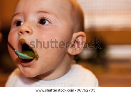 infant baby white caucasian boy eating spinach greens first foods bib brown eyes