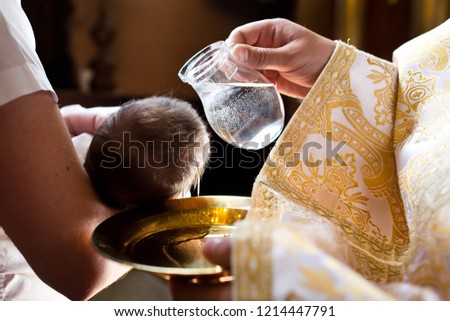 Photo of  Infant baptism. Water is poured on the head of an infant.