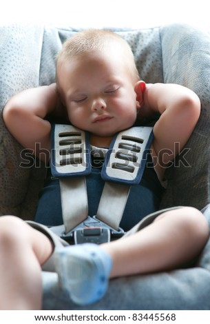 Infant boy sleeps peacefully secured with seat belts while in the car.