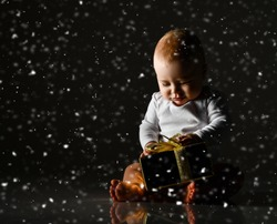 Infant child baby boy kid toddler happy smiling sitting with gold christmas present gift box for new year eve celebration with under snow on dark background