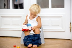 Infant child baby boy toddler sitting on potty, playing with toys in living room, indoors