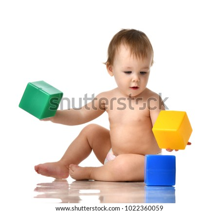 793d9ab14 Infant child baby girl toddler playing holding green blue yellow bricks toys  in hands on a
