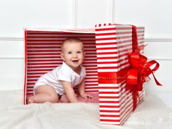 Infant child baby toddler kid sitting in big red presents gift box for celebration christmas and new year