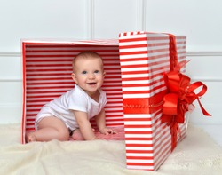 Infant child baby toddler kid sitting in presents gift for celebration. Christmas new year concept.