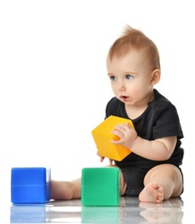 Infant child baby toddler sitting in dress with green blue and yellow brick toy playing isolated on a white background