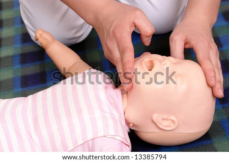 Infant dummy first aid demonstration series - First aid instructor showing how to position infant head before proceeding to mouth-to-mouth resuscitation