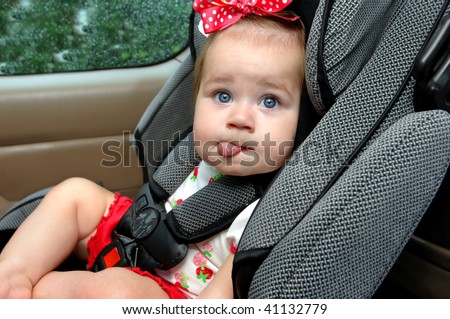 Infant expresses her dislike for child safety seats.  She is making a hilarious face with tongue sticking out.