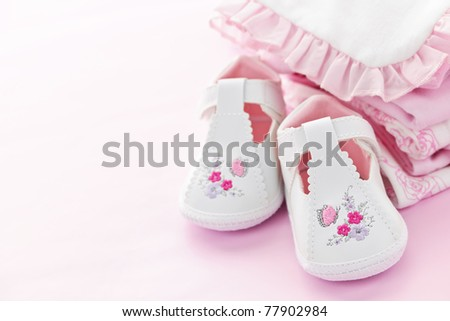 Infant girl clothing and shoes for baby shower on pink background