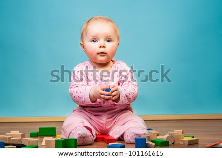 Infant girl playing in room on wooden floor