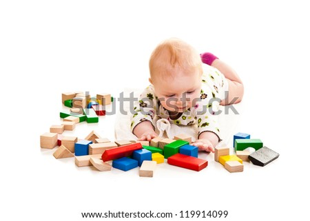Infant girl playing with building bricks isolated on white