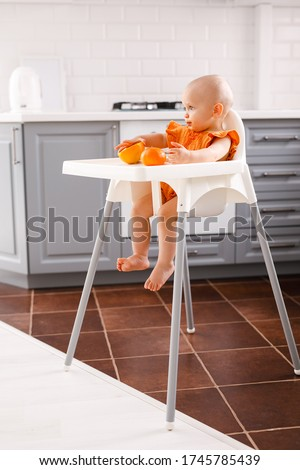 Infant girl sitting in high child's chair eating fruits on a white background. Baby food concept, space for text Stock foto ©