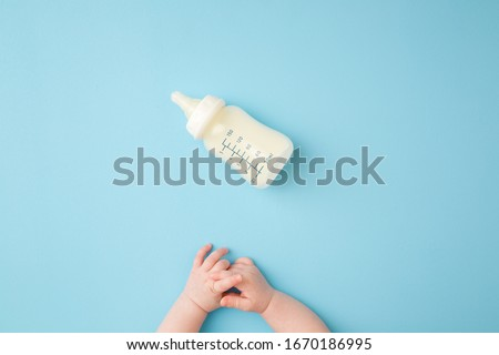 Infant hands and bottle of milk on light blue table background. Feeding time. Pastel color. Closeup. Point of view shot.