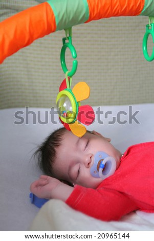 infant in red cloth sweetly sleeps