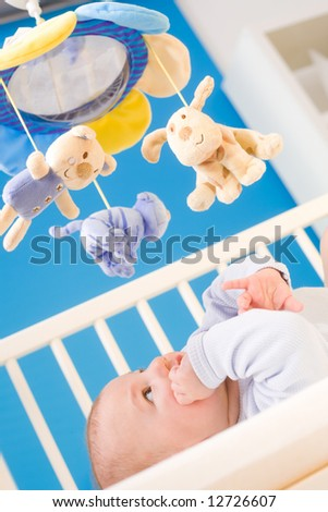 Infant paying attention to hanging toy in baby bed. Toys are officially property released. - stock photo