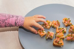 Infant reaches for tiny sandwiches with salmon and micro green