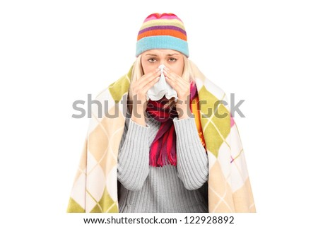 Infected woman covered with blanket blowing her nose in tissue paper because of being ill isolated on white background