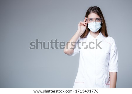Infectionist doctor in transparent glasses and a medical mask looks into the frame. Protector doctor concept on gray background.