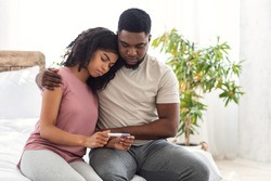Infertility concept. African sad guy hugging his wife holding negative pregnancy test, bedroom interior, free space