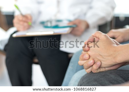 Infertility problem with marriage couple concept. A fertility doctor or reproductive endocrinologist with man and women holding hand together in therapy consult session  of inability to pregnant.