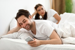 Infidelity. Cheating Husband Texting On Phone With Lover Ignoring Unhappy Jealous Wife Lying In Bed At Home. Male Cheater Having Affair. Jealousy And Unfaithfulness In Relationship. Selective Focus