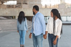 Infidelity concept. Black millennial guy distracted to another woman while walking with his girlfriend in city, selective focus