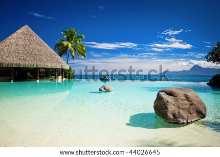 Infinity pool with artificial beach and tropical ocean