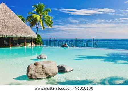 Infinity pool with palm tree overlooking tropical ocean #96010130