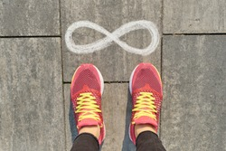 Infinity sign on gray sidewalk with woman legs in sneakers, top view.