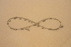 infinity symbol written on sand on the beach.