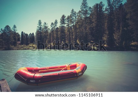 Inflatable boat on water on the river or lake near the shore in a clear summer day, the bright reflections on the waves. Red boat at the wooden bridge in the blue lake. fishing boat. rescue boat.