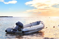 Inflatable boat with a motor in the bay at sunset