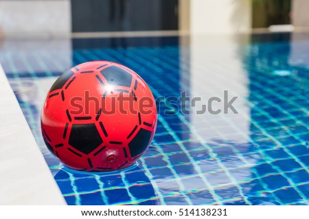Inflatable colorful ball floating in a swimming pool - Shutterstock ID 514138231