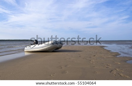 Inflatable fishing boat with an engine standing on a deserted beach on the background of blue sky with clouds. Landscape.